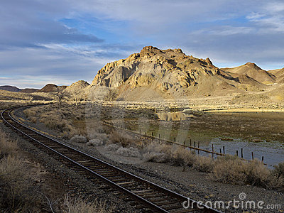 Railroad tracks running past a desert ranch