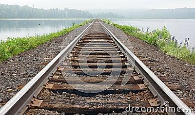 Railroad tracks vanish in the mist