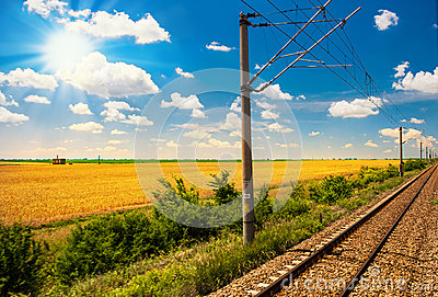 Railway goes to horizon in green and yellow landscape under blue sky with white clouds