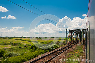 Railway and train go to horizon in green landscape under blue sky with white clouds
