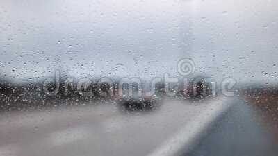 Rain water drops on the windshield in a rainy day stock video footage