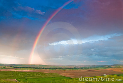 Rainbow with rain clouds and blue sky