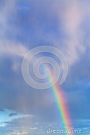 Rainbow in blue cloudy sky