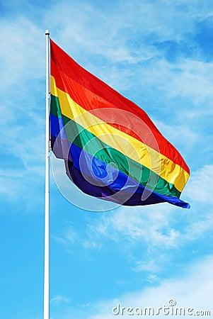 Rainbow gay pride flag on the blue sky