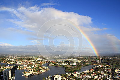Rainbow over city by river aerial view