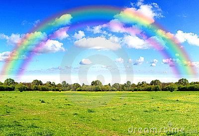Rainbow sky clouds and grass on meadow