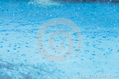 Raindrops in blue water