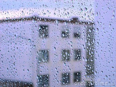 Raindrops on glass window with building view