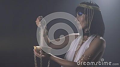 A rainha egípcia Cleopatra está guardando uma bacia dourada e uma areia de derramamento nela vídeos de arquivo