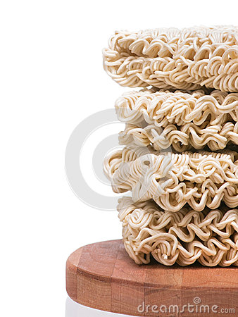 Ramen instant raw noodles staked on wooden plank