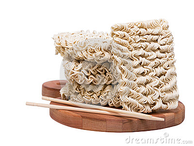 Ramen instant raw noodles on wooden plank 3/4 with chopsticks