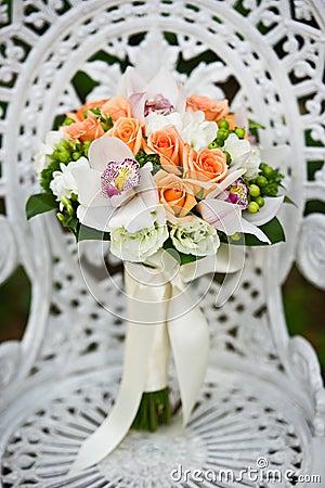 Ramo de la flor de la boda en una silla de jardín blanca