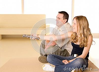 Rapariga e homem que prestam atenção à tevê