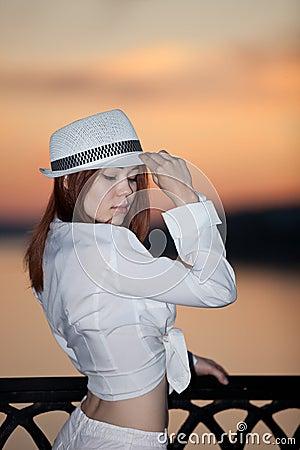 Rapariga em uma camisa e em um chapéu brancos