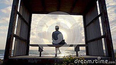 Rapariga num banco perto da costa no pôr do sol vídeos de arquivo