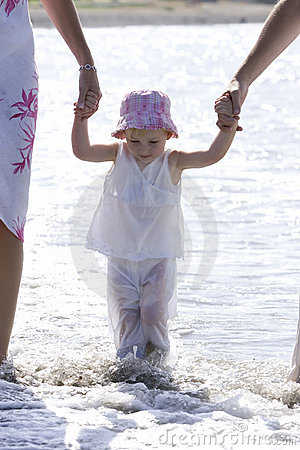 Rapariga que está sendo andada na praia por pais