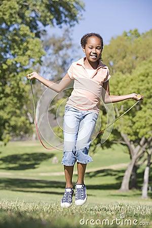 Rapariga que usa a corda de salto que sorri ao ar livre