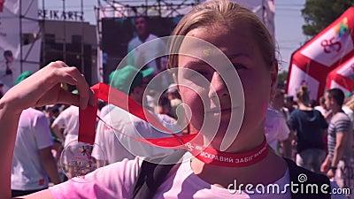 Rapariga tem uma medalha por participar do Festival Go Paint, maratona filme