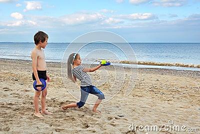 Rapaz pequeno bonito e menina, jogando na areia da praia