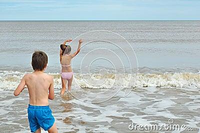 Rapaz pequeno bonito e menina, jogando na onda na praia