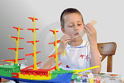 Rapaz pequeno bonito, navio do woodcraft, pintando