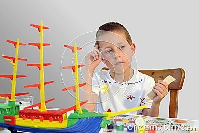 Rapaz pequeno bonito, navio do woodcraft, pintura, pensamento