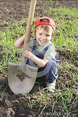 Rapaz pequeno com pá grande