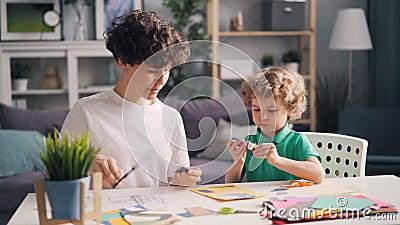 Rapaz pequeno e sua mamã que fazem a corte da colagem as figuras de papel que colam com colagem vídeos de arquivo