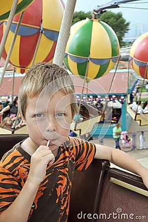Rapaz pequeno em um carrossel no parque de diversões