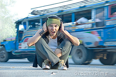 Rapper in street traffic covering ears
