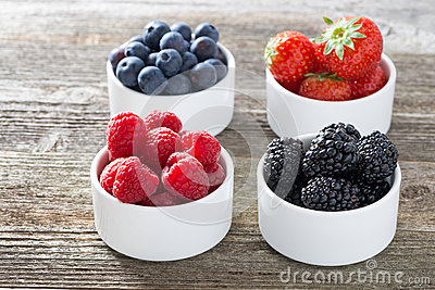 raspberries, blackberries, strawberries and blueberries in bowls