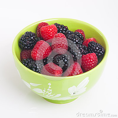 Raspberry and blackberry in green bowl on white