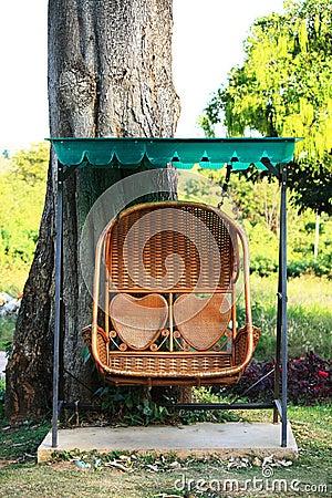 Rattan swing bench in garden