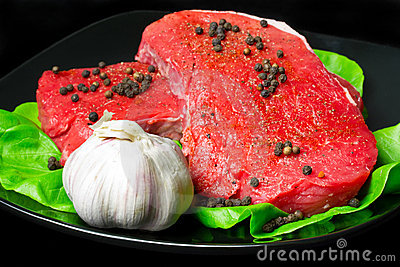 Raw beef on black plate