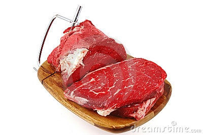 Raw beef meat chunk and slices on cutting plate
