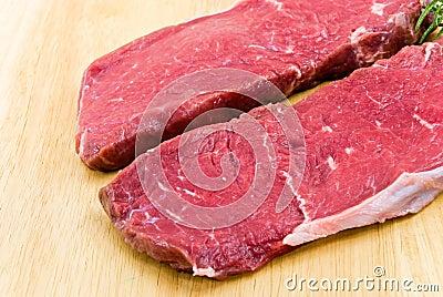 Raw beef-roast beef meat steak on the wooden backg