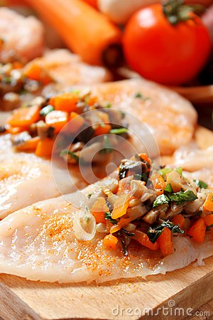 Raw chicken breast filled with vegetables garnish