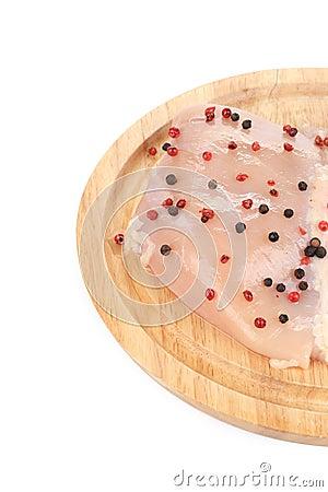 Raw chicken breast pepper on wooden board.