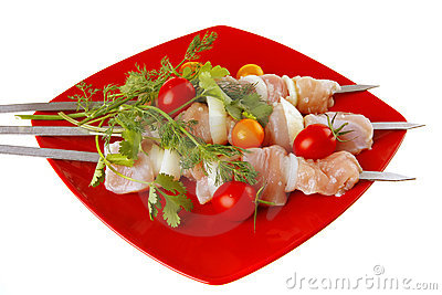 Raw chicken kebabs on red