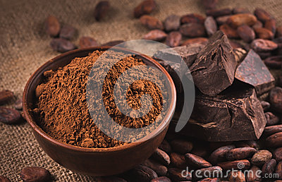 Raw cocoa beans, clay bowl with cocoa powder, chocolate on sack Stock Photo
