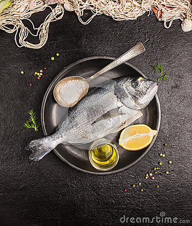 Free Raw Dorado Fish In Gray Rustic Plate With Lemon,oil And Spoon Of Salt On Dark Stone Background Stock Photo - 53057780