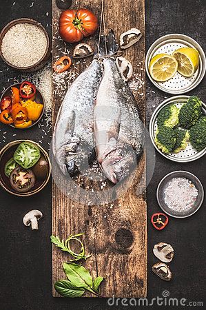 Free Raw Dorado Fishes And Healthy  Cooking Ingredients: Rice, Vegetables, Lemon. Stock Image - 81761941