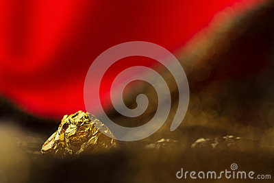 Raw Gold Nuggets On Dark Soft Glitter Red Background Royalty-Free