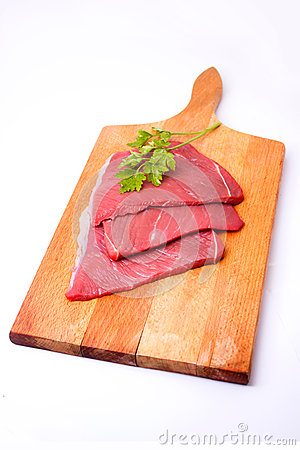 Raw meat slices on board