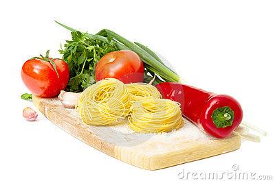 Raw pasta nest and ingredients for tomato sauce