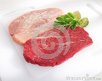 Raw pork chop and steak on cutting board. Stock Photo