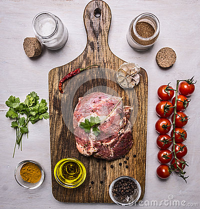 Free Raw Pork In Marinade, On A Cutting Board With Tomatoes On A Branch, Oil, Black Pepper, Herbs On Wooden Rustic Background Top View Royalty Free Stock Images - 63109469