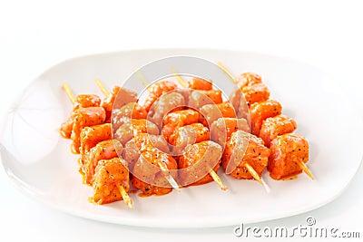 Raw skewered marinated chicken