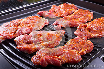 Raw steak meat on barbecue