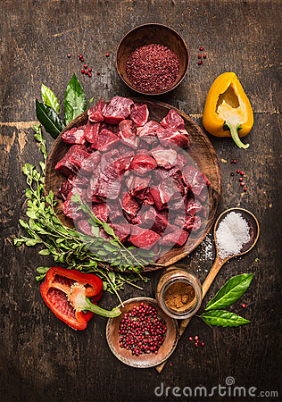 Free Raw  Uncooked Meat Sliced In Cubes With Fresh Herbs, Vegetables And Spices On Rustic Wooden Background, Ingredients For Beef Stew Stock Photos - 55977683